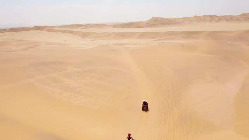 NAMIBIA, AFRICA - CIRCA 2018 - Good aerials over ATV vehicles speeding across the desert sand dunes in Namibia, Africa. #1024945961