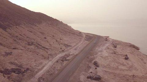 DJIBOUTI, AFRICA - CIRCA 2018 - Good aerial above a pickup truck driving on a coastal road in Somalia or Djibouti.