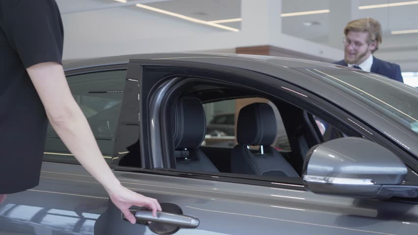 Happy couple just bought car in modern motor show. Man and woman open doors and sit inside big modern car, smiling. Concept of buying a vehicle. Car showroom. | Shutterstock HD Video #1024949741