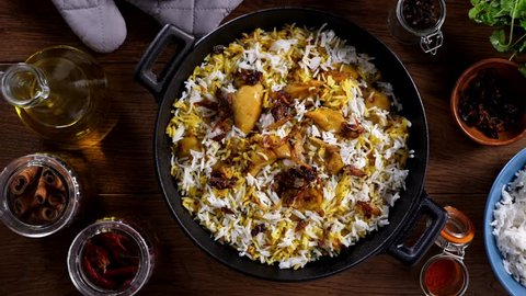Biryani with chicken. Traditional Indian dish of rice and chicken marinated in spices and yoghurt.Top view. Decorating (sprinkling) dishes with green parsley. Slow motion.