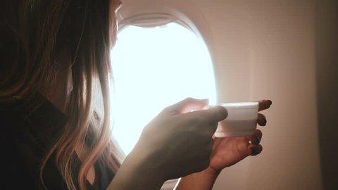 Beautiful young happy Caucasian businesswoman drinking tea, enjoying sunny view on airplane window seat during flight.