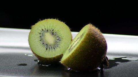 Kiwi sliced in half gyrating on black background