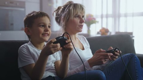 Close up cute preadolescent boy and joyful mother holding joysticks playing video game console sitting on sofa at home. Happy family spending leisure and resting together while playing home console