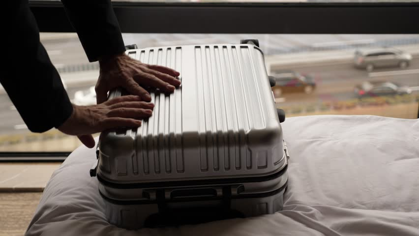 Man put hand on suitcase and push it down to close and lock. Traveller finish packing stuff and ready to leave hotel. Small trolley case lie on bed against window, car traffic seen outside blurred | Shutterstock HD Video #1025032901