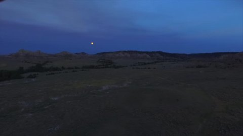 A slow cinematic drone shot panning towards the moon at dusk.