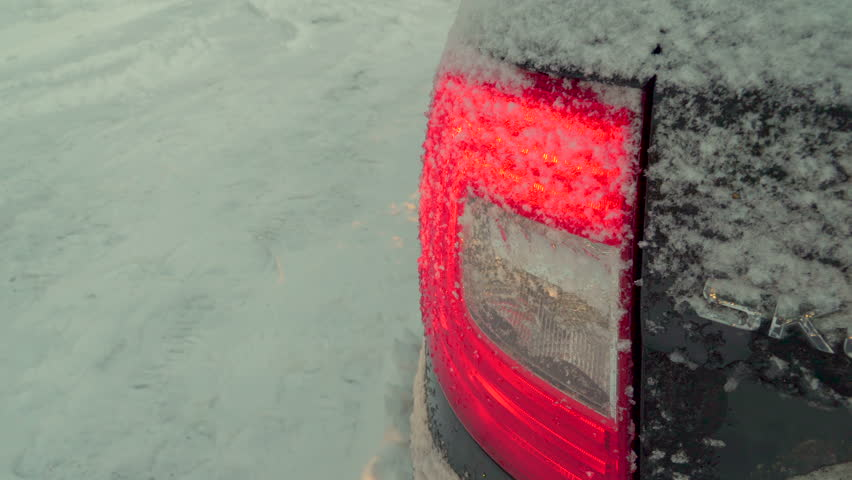 Brushing off the snow on the backlight of the car parked outside the house on a winter season | Shutterstock HD Video #1025067671