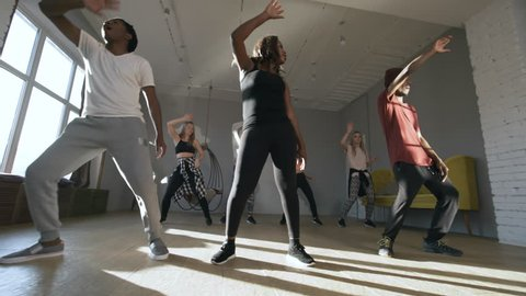 Handheld tracking shot of team of black male and female dancers teaching moves to young women in group class in sunny studio