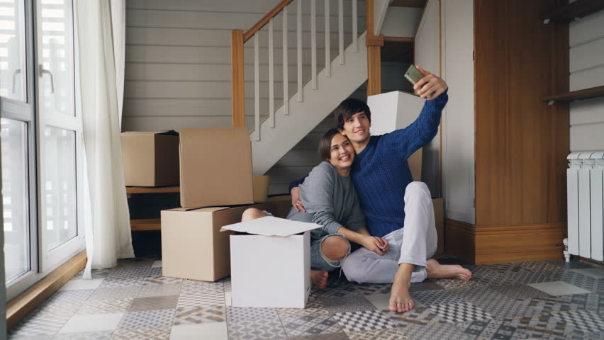 Adorable young people girl and guy are taking selfie expressing love and tenderness kissing and hugging sitting on floor of new house and using smartphone. | Shutterstock HD Video #1025077901