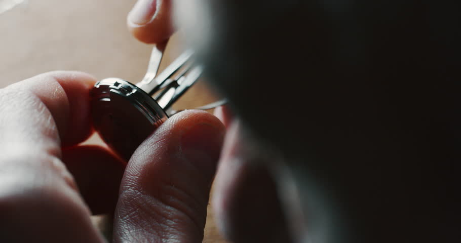 Slow motion close up of a professional watchmaker repairer working on a luxury mechanism watch gears in a workshop. Shot in 8K.