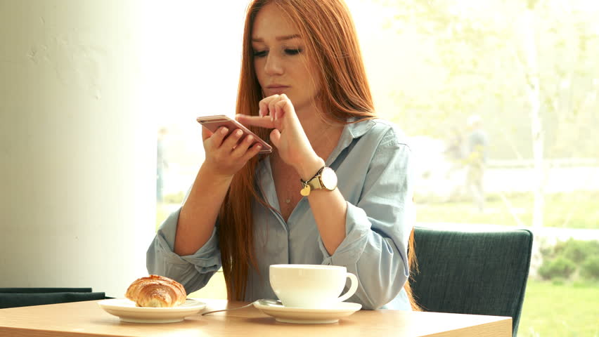 Young beautiful woman sitting with smartphone in cafe, 4K  | Shutterstock HD Video #1025268971