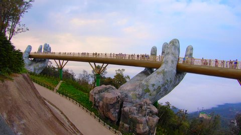 "Video Time lapse at Ba Na Hills. Da Nang, Vietnam - February 26 2019:  Tourists in Golden Bridge known as ""Hands of God"", a pedestrian footpath lifted by two giant hands"