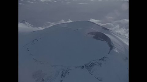 CIRCA 1973 - Aerial footage shows the snowy domes of Mount Rainier. -