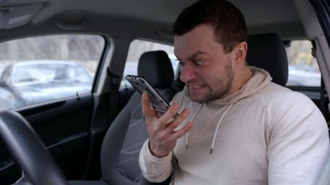 eccentric angry man is screaming and swearing on mobile phone, sitting in automobile on parking area