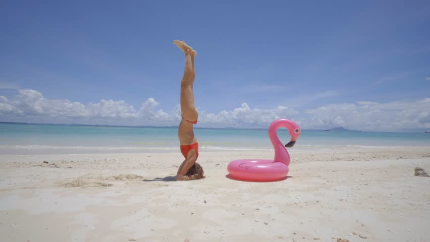 Girl exercising headstand yoga pose on idyllic beach with inflatable flamingo in pristine clear water in the Islands of Thailand. People travel luxury fun and cool attitude concept | Shutterstock HD Video #1025299871