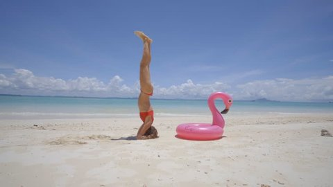 Girl exercising headstand yoga pose on idyllic beach with inflatable flamingo in pristine clear water in the Islands of Thailand. People travel luxury fun and cool attitude concept