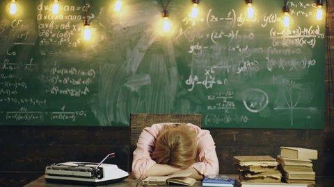 Teacher reads a book in class. Female teacher falls asleep reading a book in class. Learning concept. Teacher in classroom. Teacher and student. Back to school