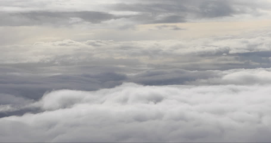 Aerial view of the heavy rain clouds high up in the sky from the airplane.
