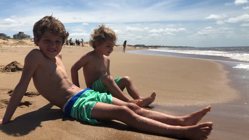 Kids seated at the beach, waiting for waves | Shutterstock HD Video #1025347691