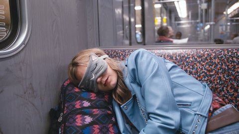 Slow Motion Young beautiful girl in the Blindfold on the eyes, fell asleep on the subway train. Head put on a backpack. The train arrives at the station. The concept of fatigue, desire to sleep.