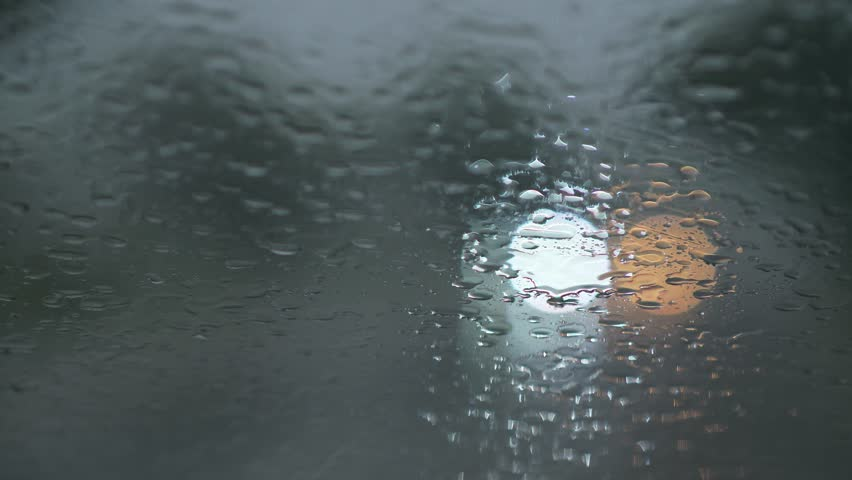 Lights of passing by car traffic seen through car windshield during rain in the evening. Windscreen wipers are wiping waterdrops from the windshield. UHD | Shutterstock HD Video #1025402681