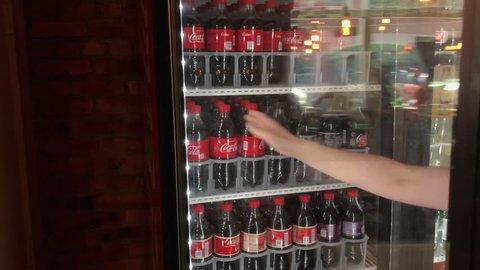 Catskill, new york - september 15: grabbing coca cola 20oz bottle from  store fridge in catskill, new york on september 15, 2018