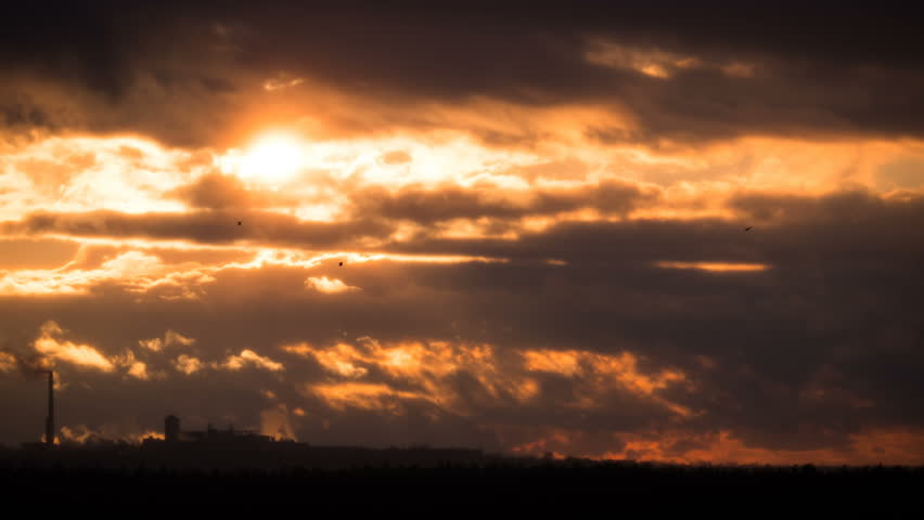 Dramatic Sunset over the Storm Clouds and Trees. Time Lapse. The dramatic landscape of sky and curly clouds. Storm clouds moving across the sky against the setting sun. The big bright red sun moves | Shutterstock HD Video #1025431961