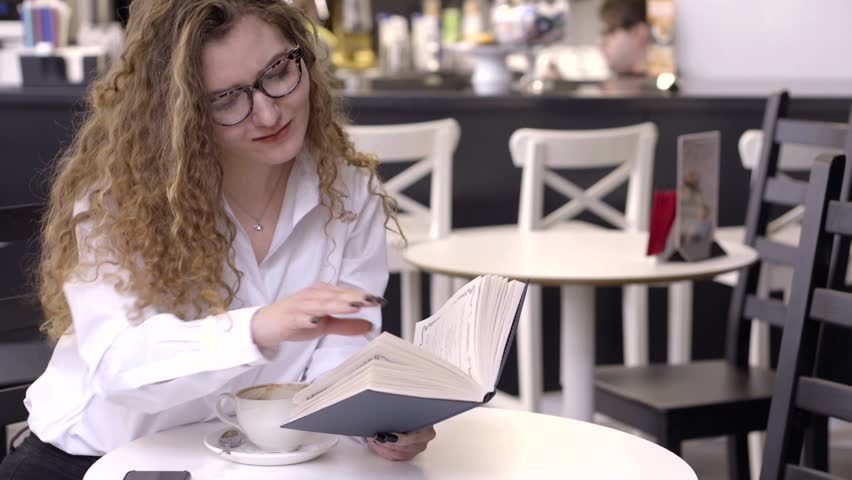 Sexy smiley girl in a white shirt and glasses reading book at the coffee table in cafe, smart young girl.