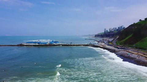 La Rosa Nautica restaurant by the sea in Makaha Beach. Group of surfers learning to surf in a bright summer day at Miraflores district, Lima, Peru.