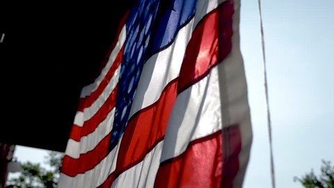 Franklin, Tennessee / United States - 07 06 2018: American flag hanging outside brick building, waving in the wind in 4K slow motion