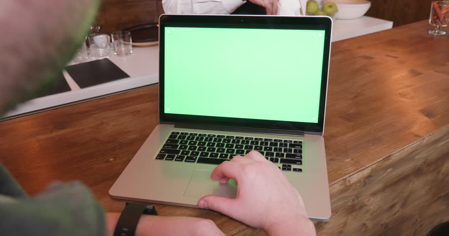 Handheld shot of working on computer with green screen at the bar counter | Shutterstock HD Video #1025550101