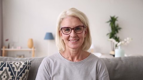Older middle aged woman waving hand looking at camera speaking to webcam making video call at home, senior mature blogger talking laughing having distant online conversation or recording vlog