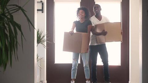 Happy black couple first time home buyers holding boxes talking embracing standing in hallway coming into big modern house, african american renters tenants relocating on moving day, family mortgage