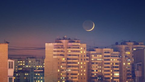 Beautiful waxing crescent moon setting behind city skyline buildings rooftops at night. Zoom in. Timelapse, 4K UHD.