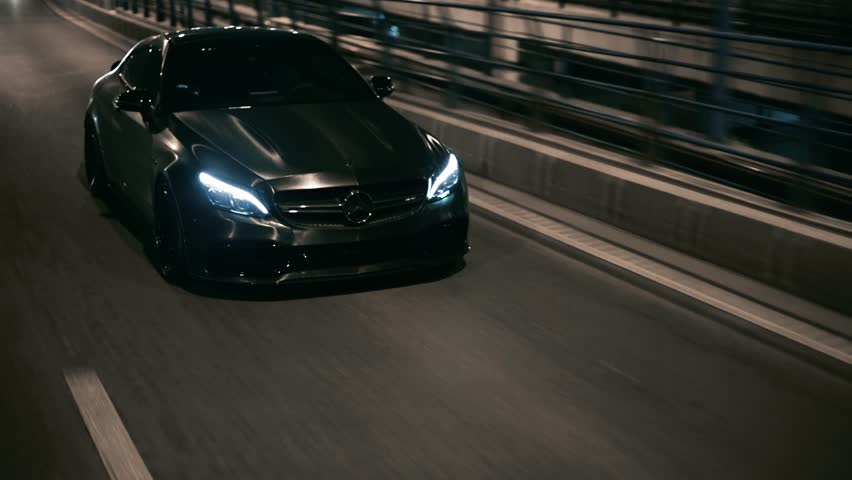 Bucharest, Romania-03.10.2018: Moving rolling shot of a black custom Mercedes C63 AMG on a city street bridge at night