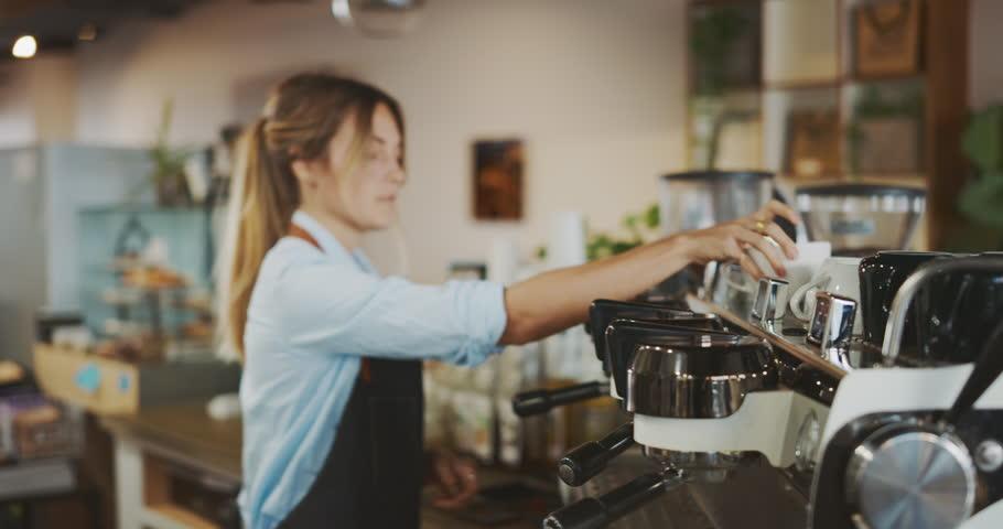 Smiling attractive female barista working in coffee shop, barista preparing espresso, artisan coffee shop lifestyle | Shutterstock HD Video #1025636981
