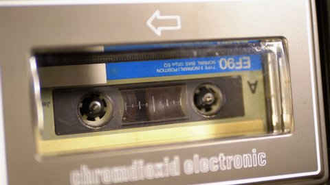 Audio Cassette in the Tape Recorder Playing and Rotates. Close-up. Vintage audio cassette tape with a blank label used for sound recording in a retro cassette player. Call recording. Macro