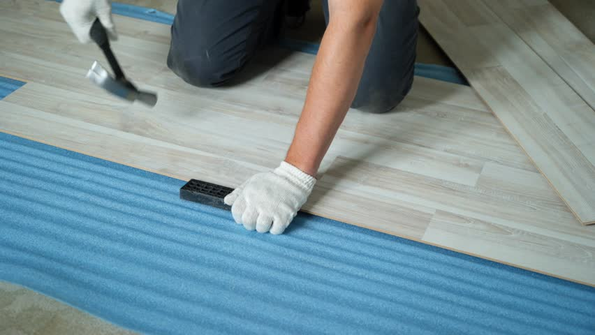 Builder renovating apartment. Repair of the apartment, laying laminate flooring. Construction. | Shutterstock HD Video #1025655911