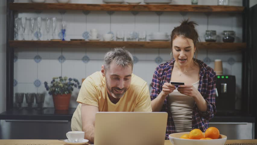 Happy couple paying for online purchases in kitchen using credit card, woman dictating credit card number to her boyfriend. Happy shopping