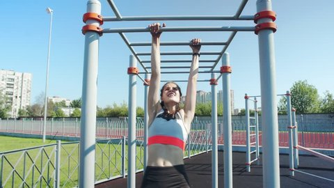 Fit teenage girl performing monkey bars climbing exercise, recovering and stretching after it