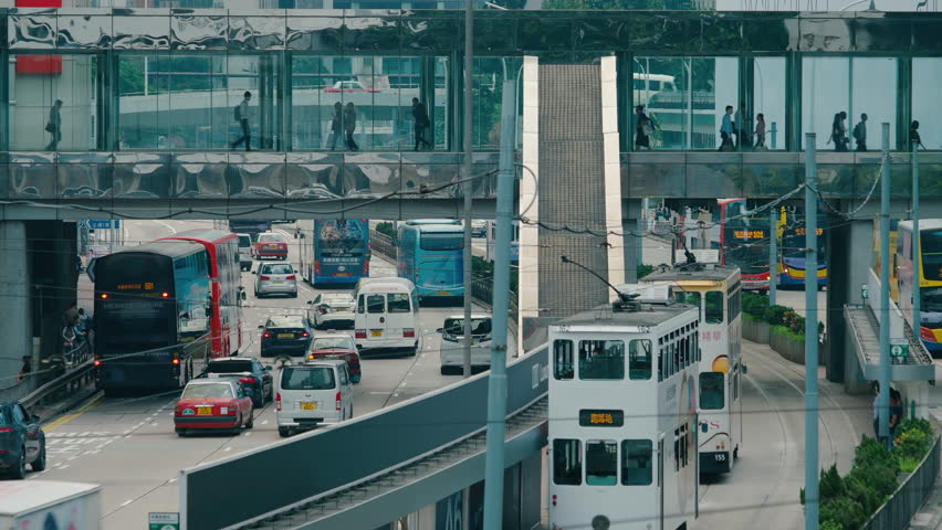 Hong Kong- November 12,2018: Time lapse of busy De Voeux Road in Central. Long lens shot of busy road with vehicles and trams and an overhead pedestrian walkway | Shutterstock HD Video #1025732201