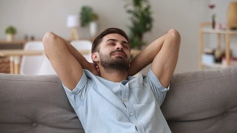 Calm happy young man relaxing with eyes closed or having healthy nap on comfortable couch breathing fresh air, lazy tired guy enjoying stress free peaceful day feeling harmony lounge at home on sofa