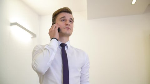 Young business man in white shirt and tie talking by mobile phone on white background. Handsome man entrepreneur calling smartphone in business office. Male portrate low angle