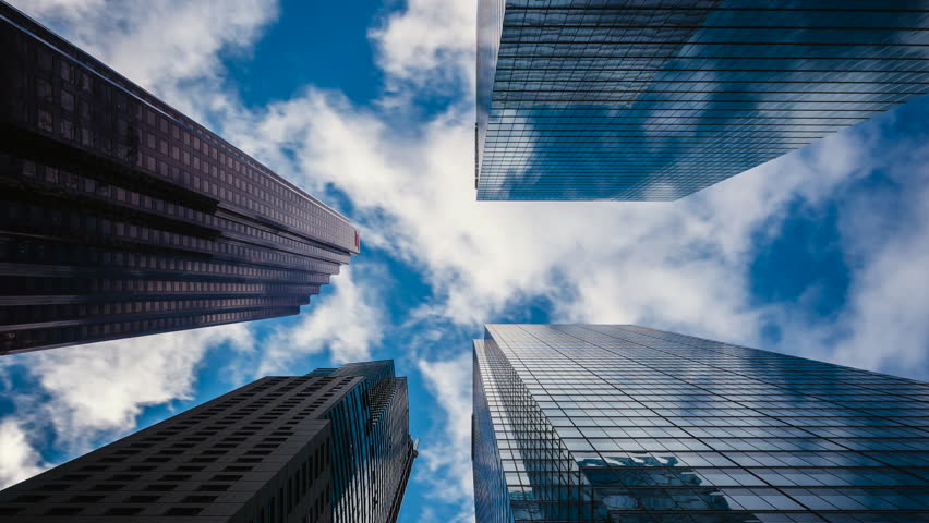 Downtown Toronto time lapse view, looking up at office buildings in the financial district of Toronto in Ontario, Canada, clouds passing in the background.
