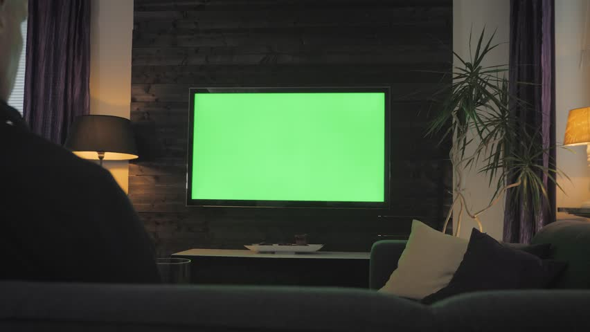 Green Screen - Man watching TV on a couch in the living room. Over the shoulder shoot.   Shutterstock HD Video #1025751191