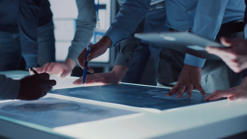 Engineer, Scientists and Developers Gathered Around Illuminated Conference Table in Technology Research Center, Talking, Finding Solution and Analysing Industrial Engine Design. Close-up Hands Shot | Shutterstock HD Video #1025767421