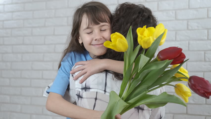 Mothers Day. A little girl gives flowers to mother. | Shutterstock HD Video #1025828141