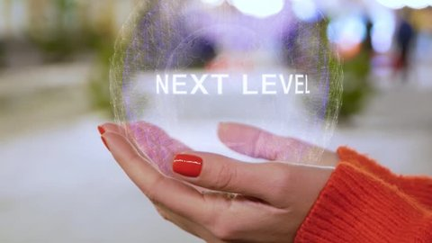 Female hands holding a conceptual hologram with text Next level. Woman with red nails and sweater with future holographic technology on a blurred background of the street