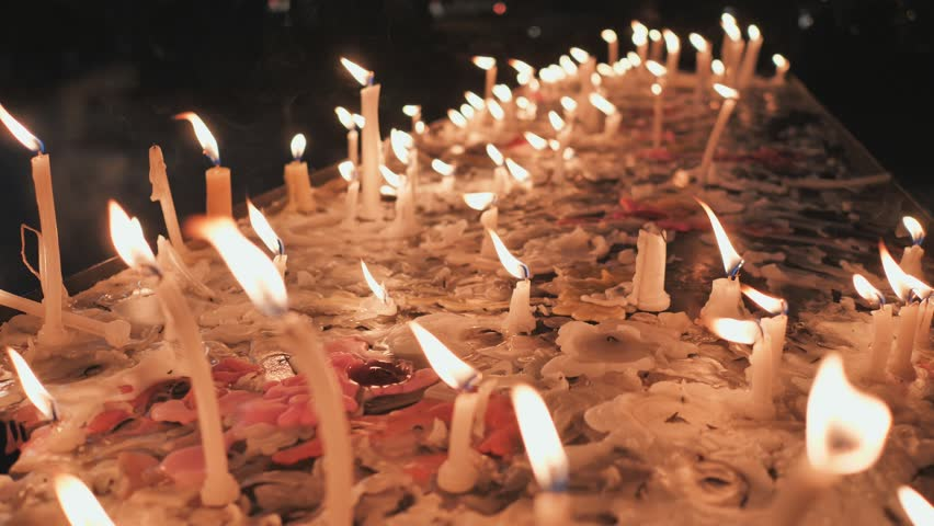 Church candles are burning against the background of melted wax on the table.   Shutterstock HD Video #1025866601