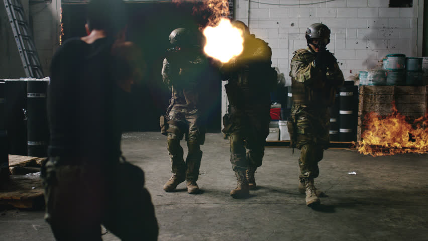 Playback movie or commercial of armed SWAT police team enter a warehouse that's on fire shooting bad guys from a gang with rifle guns with VFX. Wide shot on 4k RED camera.