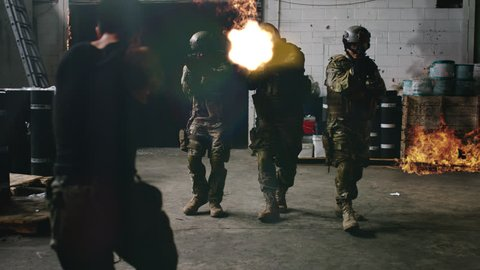 Armed SWAT police team enter a warehouse that's on fire shooting bad guys from a gang with rifle guns with VFX. Wide shot on 4k RED camera.